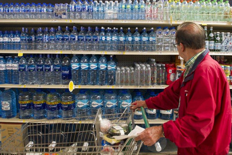 hombre con coche mirando los altos precios de agua embotellada saludable