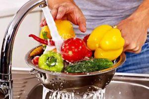 hombre lavando desinfectando en agua pura verduras pimientos en varias colores para preparar comida saludable