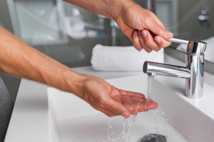 hombre usando sus manos para servir agua y probar el agua en casa
