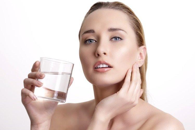 mujer con piel brillante hidratación y agua conseguidos por tomar agua