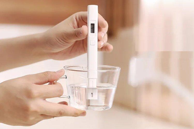 una mujer agarrando un medidor de tds del agua probando agua potable en un vaso de vidrio en su cocina